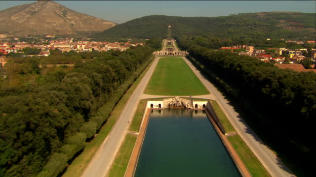 Aerial over fountains, ponds and cascades along canal in garden of Royal Palace at Caserta / Italy