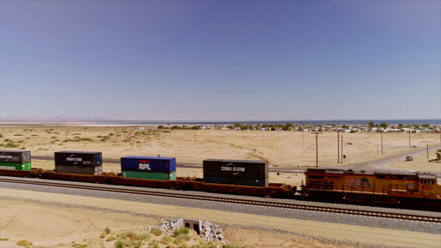 ws aerial over freight train passing california highway 111 near open desert and city of bombay beach - san andreas fault stock videos & royalty-free footage