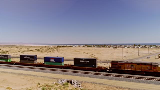 ws aerial over freight train passing california highway 111 near open desert and city of bombay beach - faglia di sant'andrea video stock e b–roll