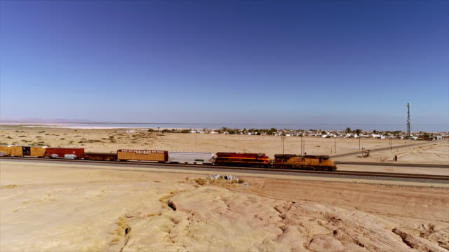 ws aerial over freight train pulling box cars through open desert and highway intersection at the entrance to city of bombay beach - faglia di sant'andrea video stock e b–roll