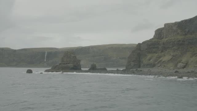 vidéos et rushes de aerial over green highlands, ocean and rocky cliffs; isle of skye, scotland, uk - îles hébrides