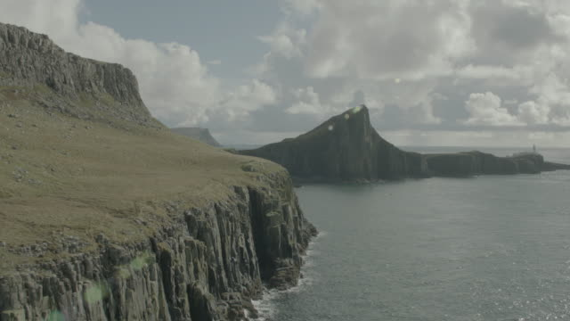 vídeos de stock, filmes e b-roll de aerial over green highlands, ocean and rocky cliffs; isle of skye, scotland, uk - escócia