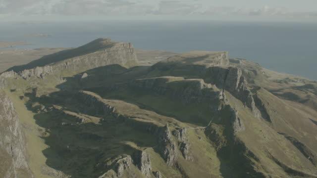 aerial over green highlands, ocean and rocky cliffs; isle of skye, scotland, uk - ハイランド地方点の映像素材/bロール