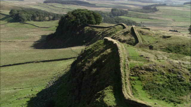 vidéos et rushes de aerial over hadrian's wall on hill in english countryside / northumberland, england - nord est de l'angleterre