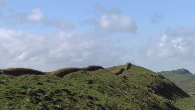 aerial over hadrian's wall on ridge of hill to reveal body of water on other side / england - northumberland video stock e b–roll
