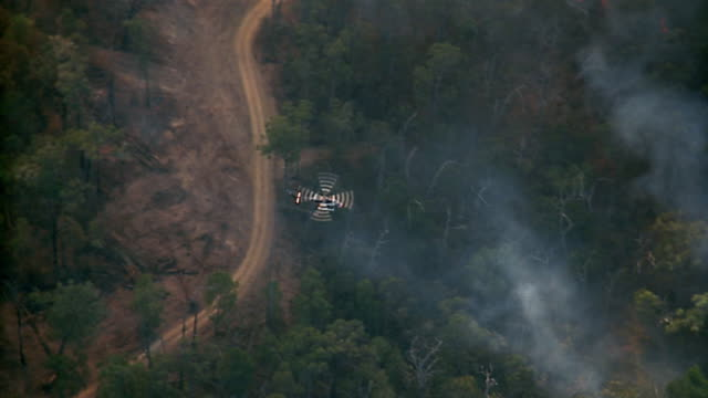 aerial over helicopter sparying water on forest fire / lysterfield, australia - melbourne australia stock videos & royalty-free footage