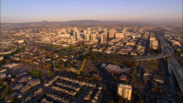 Aerial over highway and houses towards skyscrapers downtown / Oakland, California