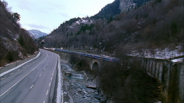 aerial over highway following passenger train through tunnels in the swiss alps / switzerland - passenger train stock videos & royalty-free footage