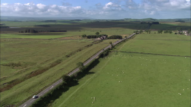 Aerial over highway on ancient Roman supply route through countryside / Northumberland, England