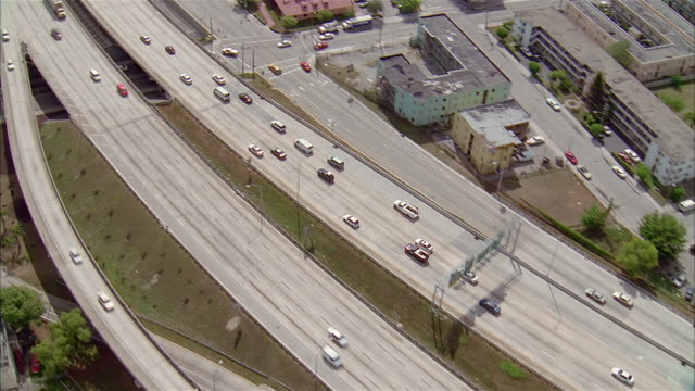 aerial over highway overpasses / following traffic on highway / zoom in to red suv / miami, florida - miami stock videos & royalty-free footage