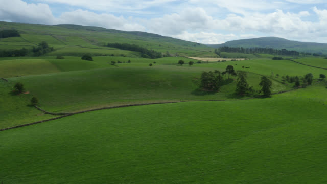aerial over hills, fields and countryside, cumbria, uk - land stock videos & royalty-free footage