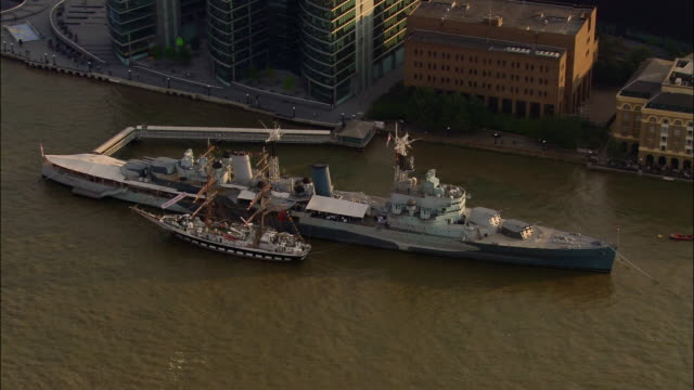 aerial over hms belfast berthed on bank of thames / london - belfast stock-videos und b-roll-filmmaterial