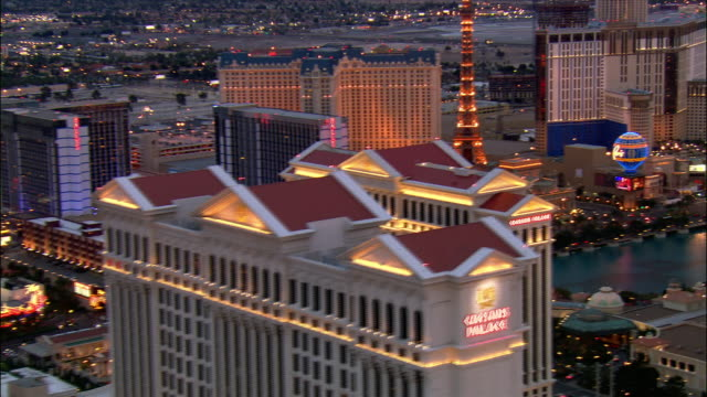 aerial over hotels and casinos along las vegas strip at dusk / las vegas, nevada - replica della torre eiffel video stock e b–roll
