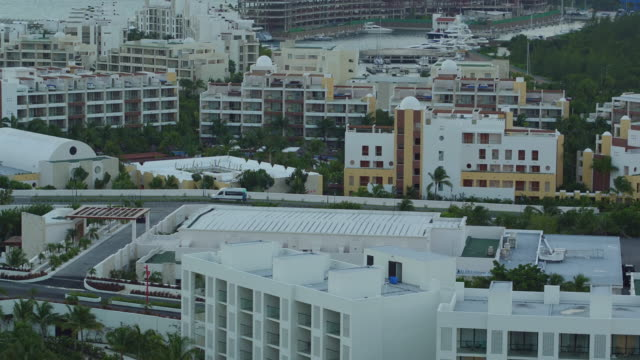 aerial over hotels in cancun, panning out to marina and light blue ocean - cancun stock videos & royalty-free footage