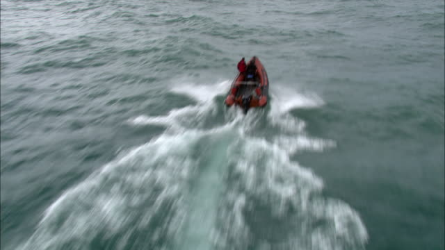 Aerial over Inflatable rib boat powering across sea, Cornwall, UK