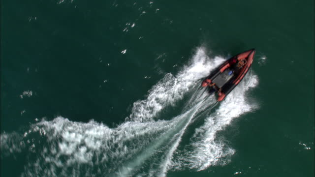 aerial over inflatable rib boat powering across sea, cornwall, uk - nautical vessel stock videos & royalty-free footage