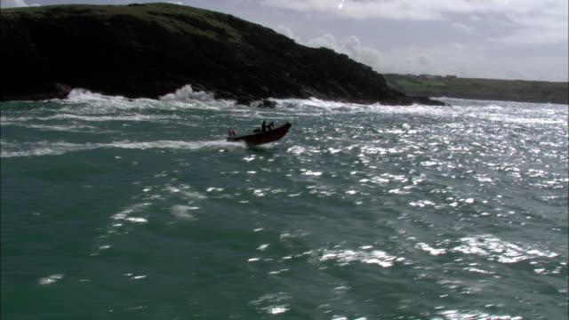 Aerial over Inflatable rib boat powering across sea near coast, Cornwall, UK