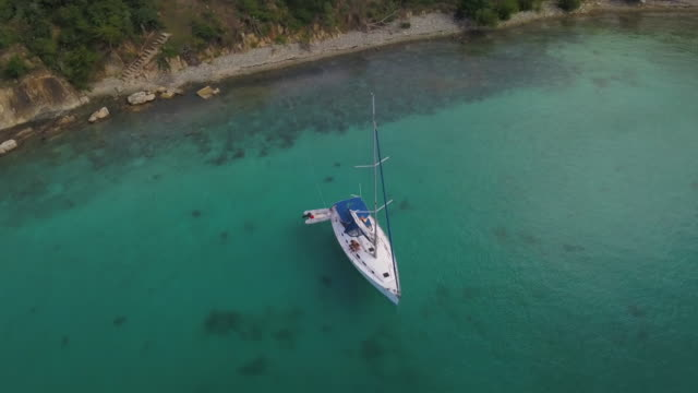 aerial: over island in caribbean past hurricane-damaged house to boat in bay in st. croix, us virgin islands - anchored stock videos & royalty-free footage
