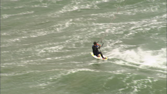 aerial over kite surfer on bournemouth beach, dorset, uk - bournemouth england stock videos & royalty-free footage