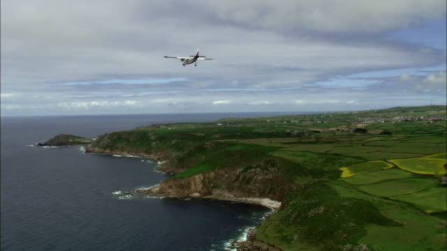 aerial over light aircraft flying over coast, cliffs and sea, cornwall, uk - aeroplane stock videos & royalty-free footage