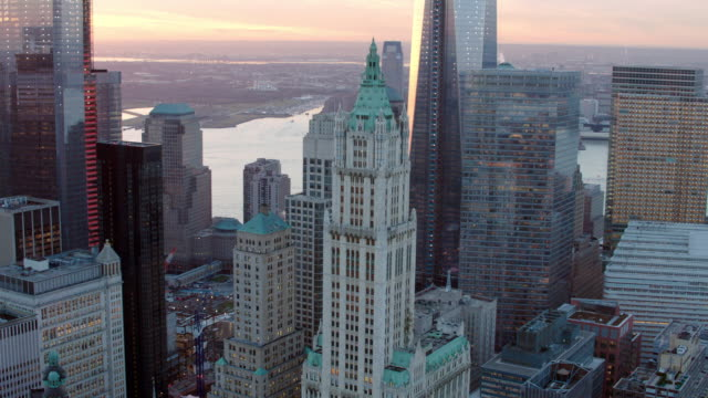 aerial over lower manhattan, flying around woolworth building with one world trade center behind at sunset - woolworth building stock videos & royalty-free footage
