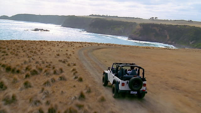 aerial over man and woman in jeep / flinders, mornington peninsula, australia - 四輪駆動車点の映像素材/bロール