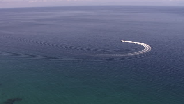 Aerial over motor boat on sea and forested coast, Madagascar