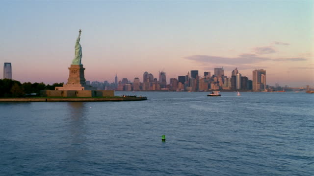 Aerial over New York Harbor past Statue of Liberty to Manhattan skyline at dusk / New York City