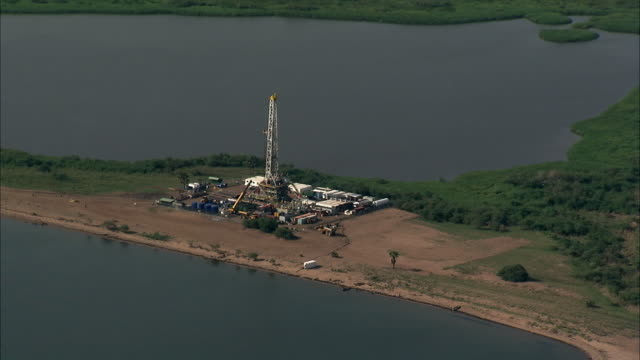 aerial over oil derrick on shore of lake albert, uganda - land stock videos & royalty-free footage