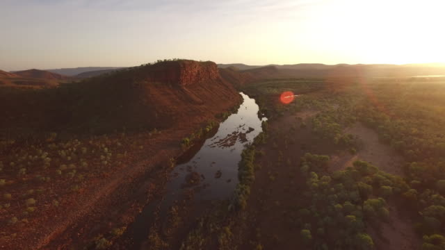 aerial over outback mountain range and river at sunset - arid stock videos & royalty-free footage
