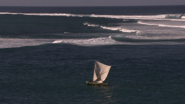 Aerial over outrigger sailing near breakers on coast, Madagascar