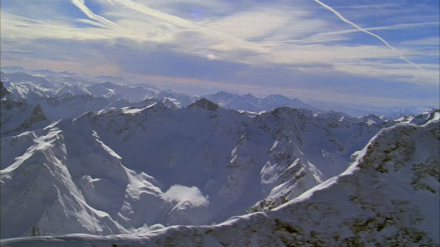 aerial over peaks of snow-covered mountains in alps / switzerland - schneebedeckt stock-videos und b-roll-filmmaterial