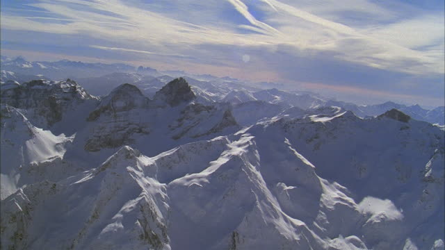 aerial over peaks of snow-covered mountains in alps / switzerland - schweizer alpen stock-videos und b-roll-filmmaterial