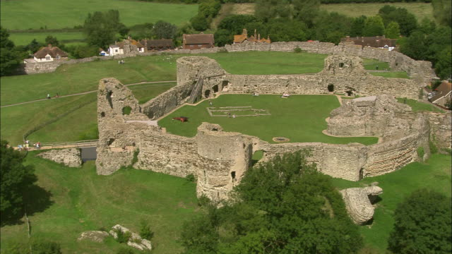 aerial over pevensey castle / zoom out landscape / east sussex, england - イーストサセックス点の映像素材/bロール