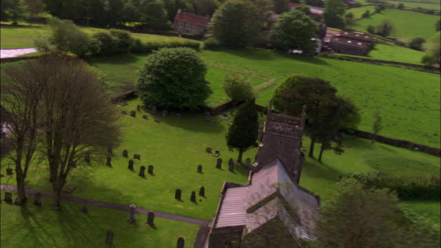 Aerial over Priddy Church and graveyard, Somerset, UK