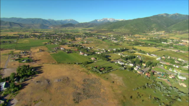 Aerial over residential homes nestled in valley / Heber City, Utah