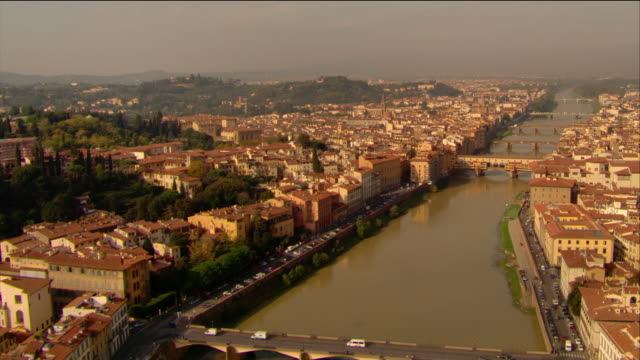aerial over river arno from east / over ponte vecchio and other bridges / florence, italy - florence stock videos and b-roll footage