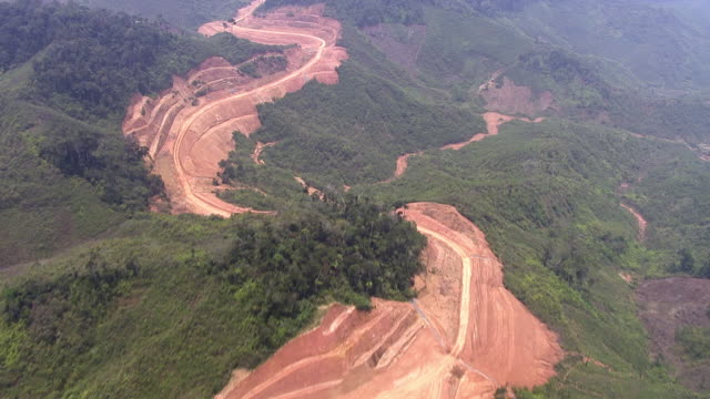 Aerial over road building on deforested mountainside, Madagascar