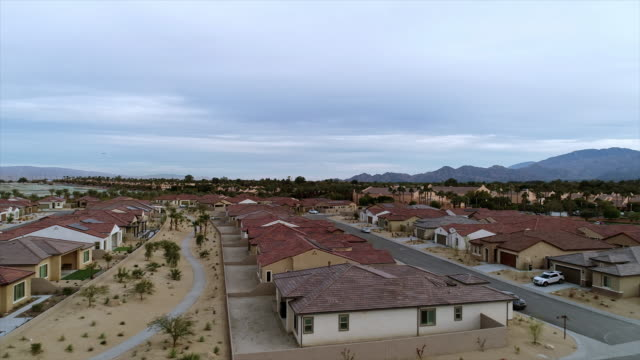 ws aerial over roof tops of brand new homes in master planned adult living gated community - rancho mirage stock videos & royalty-free footage