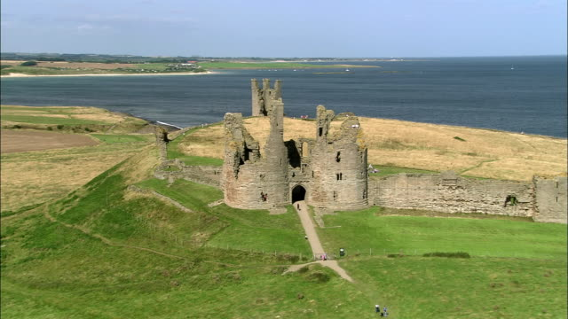 aerial over ruins of dunstanburgh castle on coast of northumberland / craster, england - northumberland coast stock videos & royalty-free footage