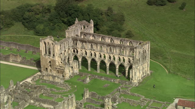 stockvideo's en b-roll-footage met aerial over ruins of rievaulx abbey / rievaulx, north yorkshire, england - rond de 12e eeuw
