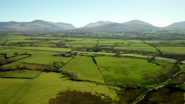 aerial over rural farmland and countryside in caernarfon north wales - field stock videos & royalty-free footage