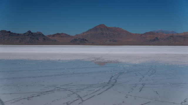 vidéos et rushes de aerial over salt flats with water below - utah