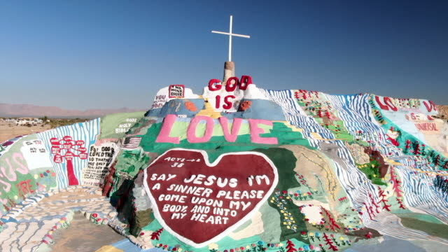 aerial over salvation mountain on sunny day with stretches of desert and mountains - film festival stock videos & royalty-free footage