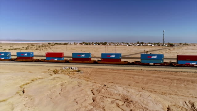 ws aerial over san andreas earthquake fault line near freight train passing through open desert and city sign at the entrance to bombay beach - western usa stock videos & royalty-free footage