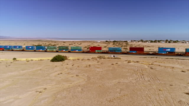 ws aerial over san andreas earthquake fault line near freight train passing through open desert and city of bombay beach - faglia di sant'andrea video stock e b–roll
