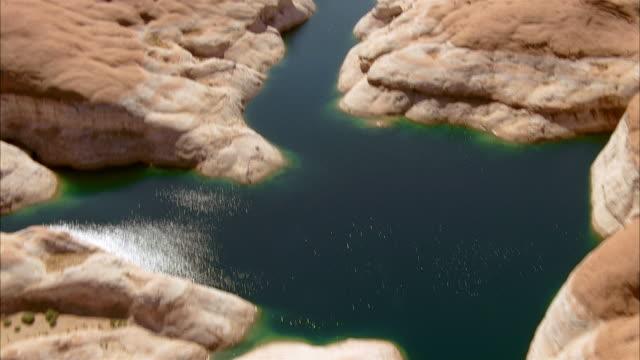 vídeos de stock, filmes e b-roll de aerial over sandstone rock formations in lake powell - lake powell