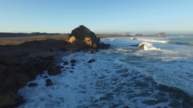 aerial over sea towards rocky outcrop, namibia, 2015 - namibia stock videos & royalty-free footage