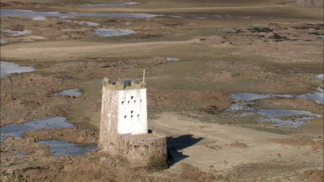 Aerial over Seymour Tower and coast at low tide, Jersey, UK