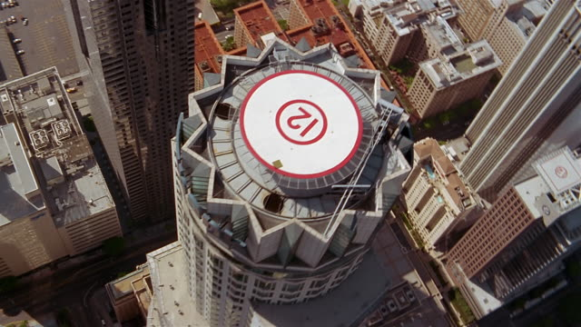 Aerial over skyscapers in downtown Los Angeles and helipads on top of US Bank building